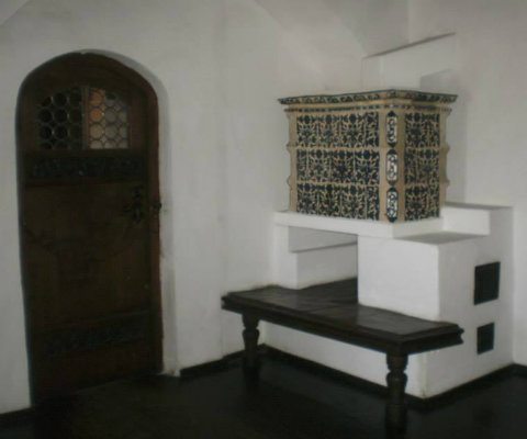 Amenajare semineu pe colt cu partea superioara decorata cu teracota cu modele florale iar in fata cu lavita